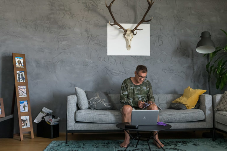 Armin Assinger der in einem schönen Raum auf einer Couch mit Laptop, Notziblock und Stift sitzt