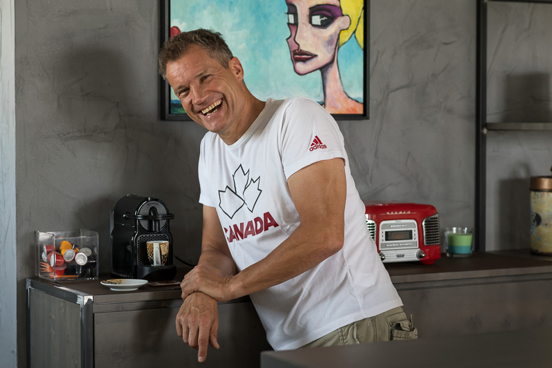 Armin Assinger der sich gerade einen Kaffee an einer Kapselkaffeemaschine macht.