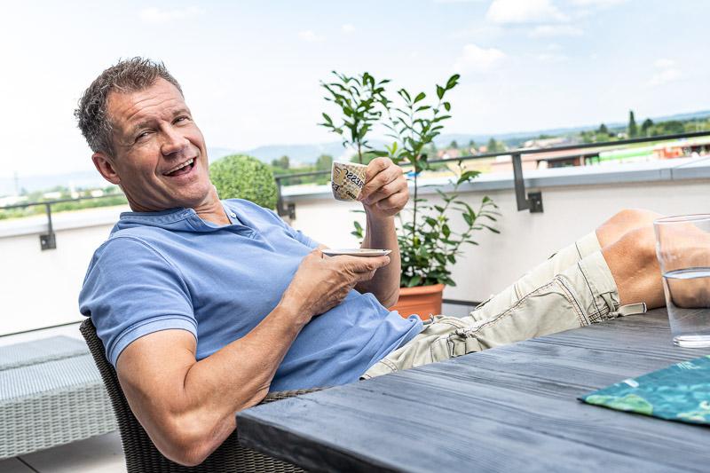 Armin Assinger lachend mit einer Tasse Kaffee